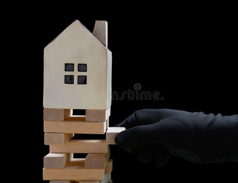 Mano con guanto nero che danneggia le fondamenta di una casa e la casa sta per cadere fotografia stock libera da diritti