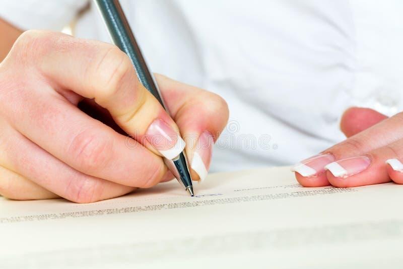 Mano con il contratto di firma della penna stilografica immagini stock libere da diritti