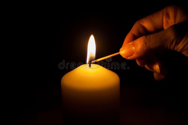 Mano con il fiammifero, accendente una candela fotografia stock
