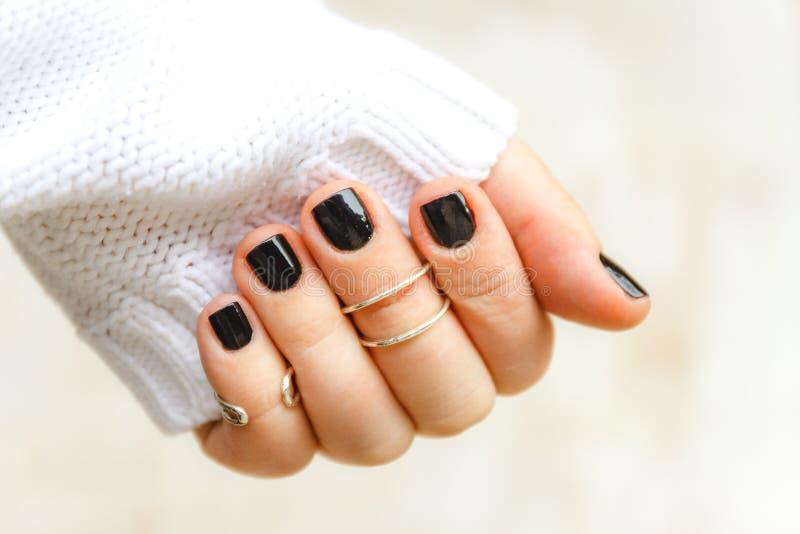 mano con il manicure e gli anelli neri sulle falangi sulle brevi unghie in un maglione bianco su un fondo leggero Il concetto del immagini stock libere da diritti