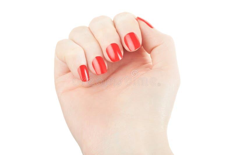 Mano con il manicure e lo smalto rosso fotografie stock