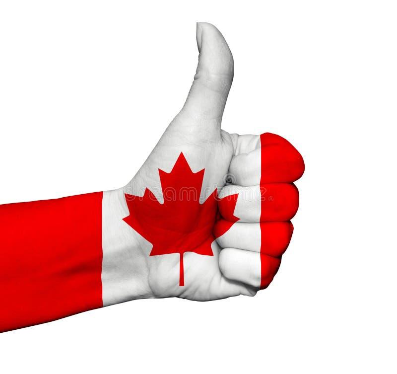 Mano con il pollice su dipinto a colori della bandiera del Canada isolato immagine stock libera da diritti