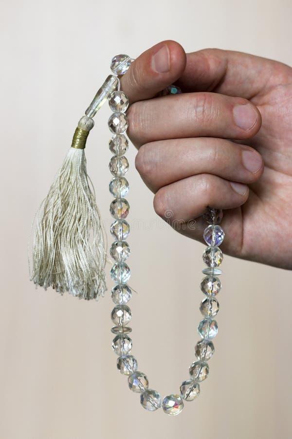 Mano con il tasbih musulmano delle perle del cristallo di rocca immagini stock libere da diritti