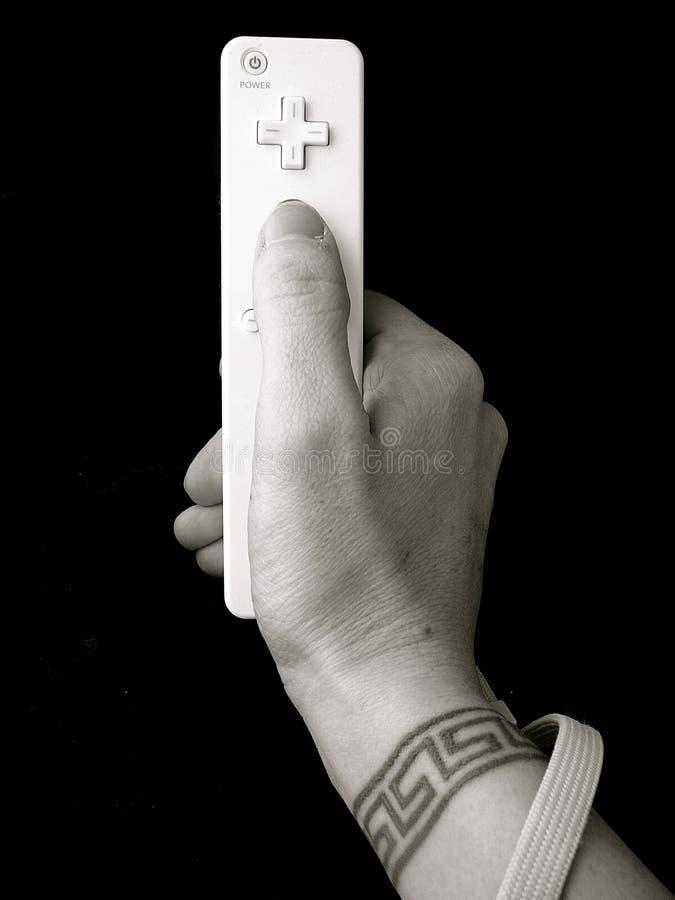 Mano con il tatuaggio della manopola che tiene controllo del video gioco fotografia stock libera da diritti