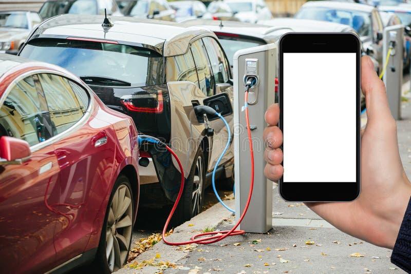 Mano con il telefono su un fondo delle automobili elettriche che fanno pagare i punti fotografia stock