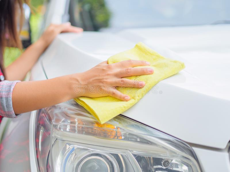 Mano con l'automobile bianca di pulizia del panno giallo del microfiber fotografie stock
