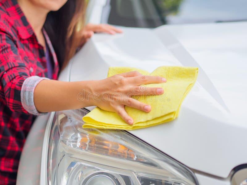 Mano con l'automobile bianca di pulizia del panno giallo del microfiber fotografia stock libera da diritti