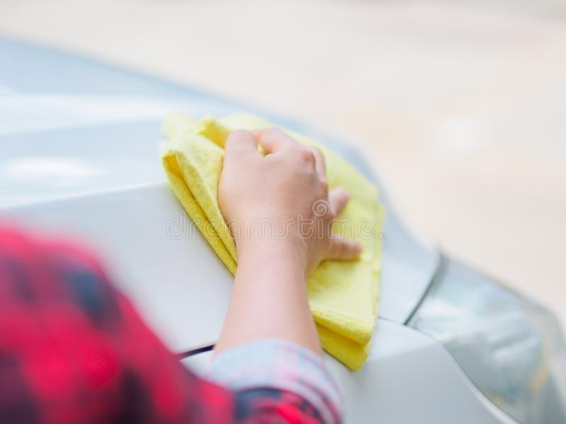 Mano con l'automobile bianca di pulizia del panno giallo del microfiber immagini stock