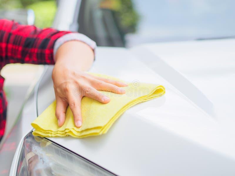 Mano con l'automobile bianca di pulizia del panno giallo del microfiber immagine stock libera da diritti