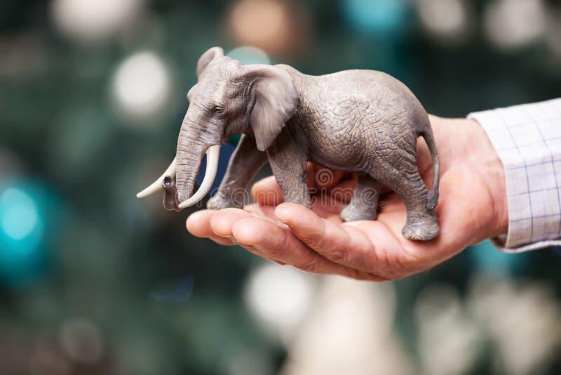 Mano con l'elefante del giocattolo sul fondo di Natale immagini stock