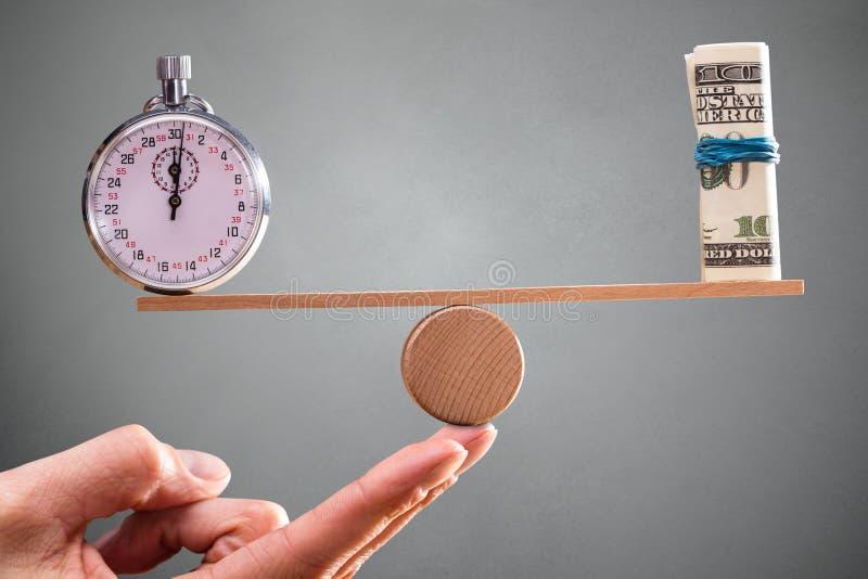 Mano con la balanza entre el cronómetro y rodada encima de billetes de banco foto de archivo