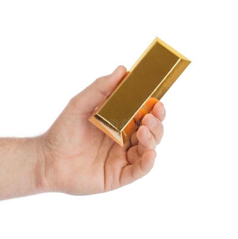 Mano con la barra de oro fotografía de archivo libre de regalías