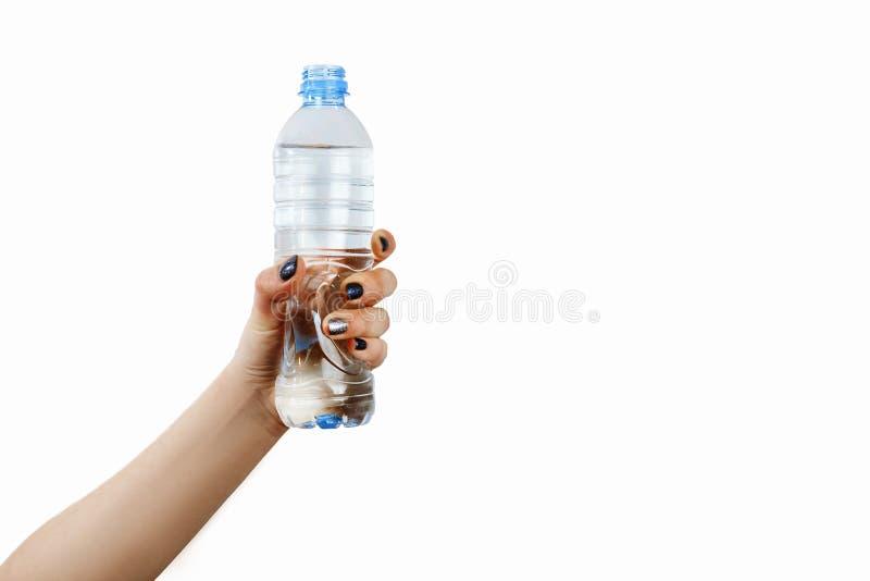 Mano con la botella de esquina, muchacha que sostiene una botella de agua en su mano, pequeña botella, aislada foto de archivo