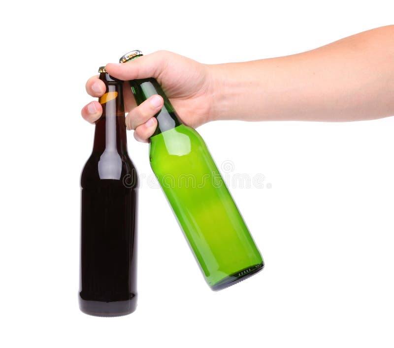 Mano con la botella dos de cerveza en un fondo blanco imagen de archivo
