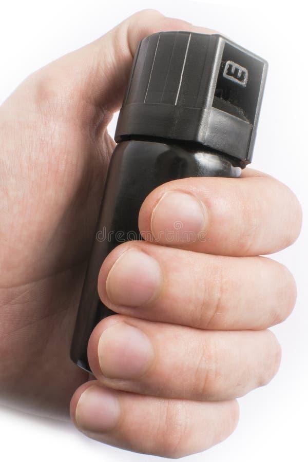 Mano con la bottiglia di spray al pepe isolata su fondo bianco immagine stock libera da diritti