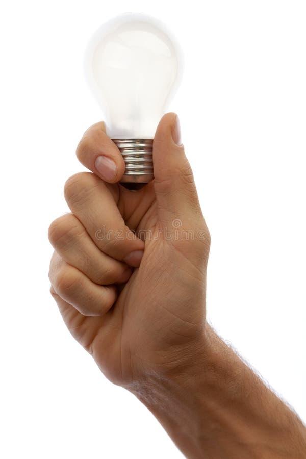 Mano con la lampada isolata su priorità bassa bianca fotografia stock libera da diritti