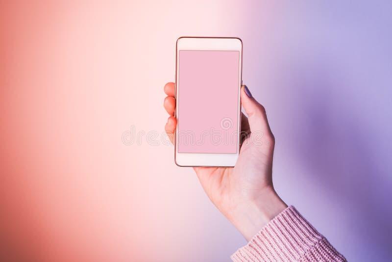 Mano con la pantalla del teléfono móvil en rosa y púrpura fotos de archivo libres de regalías