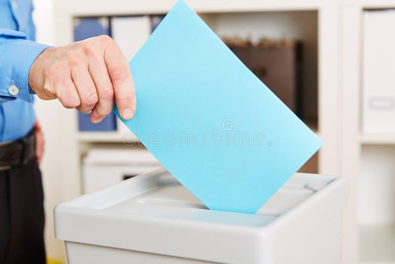 Mano con la papeleta electoral durante la elección foto de archivo libre de regalías