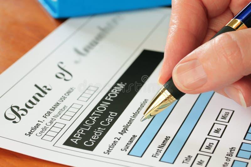 Mano con la pluma que firma el impreso de la tarjeta de crédito imagenes de archivo