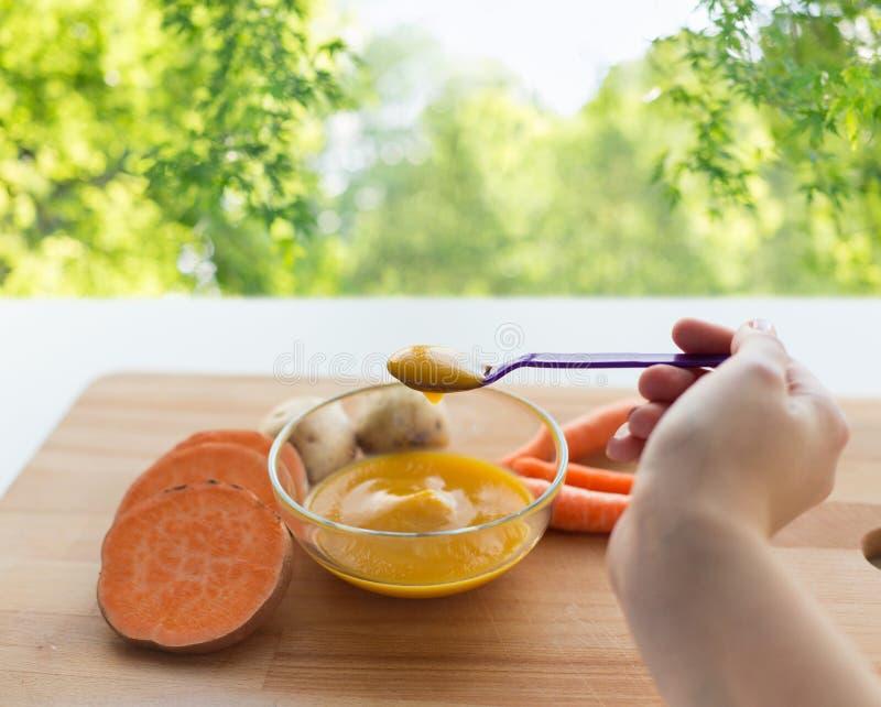 Mano con la purea di vegetali o gli alimenti per bambini in cucchiaio fotografie stock libere da diritti