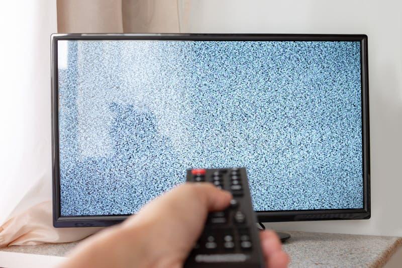 Mano con la TV teledirigida delante de la pantalla con el ruido blanco en él - adaptación de las cadenas de televisión y conexión fotos de archivo libres de regalías