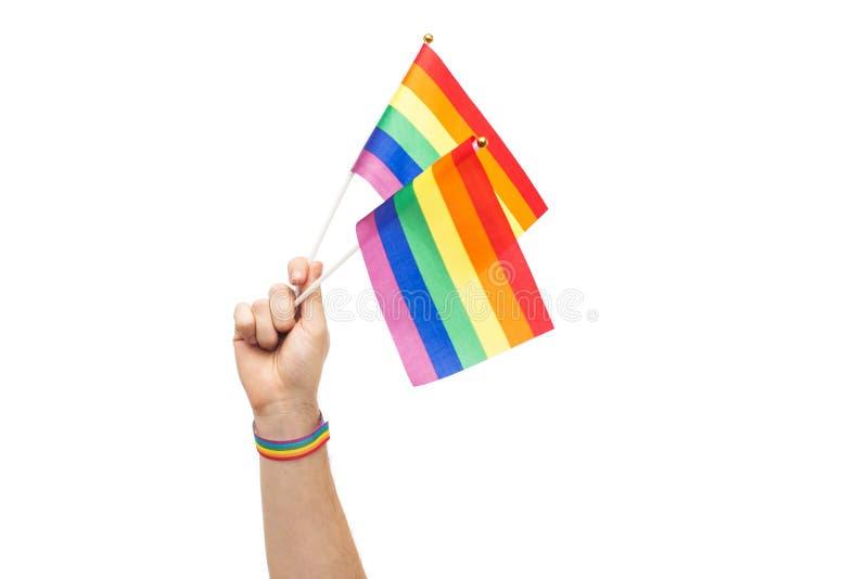 Mano con las banderas y pulsera del arco iris del orgullo gay imágenes de archivo libres de regalías