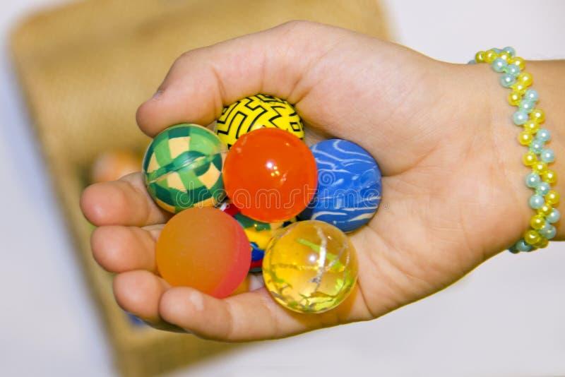 Mano con las bolas coloridas y caja por completo de bolas coloridas imagen de archivo libre de regalías