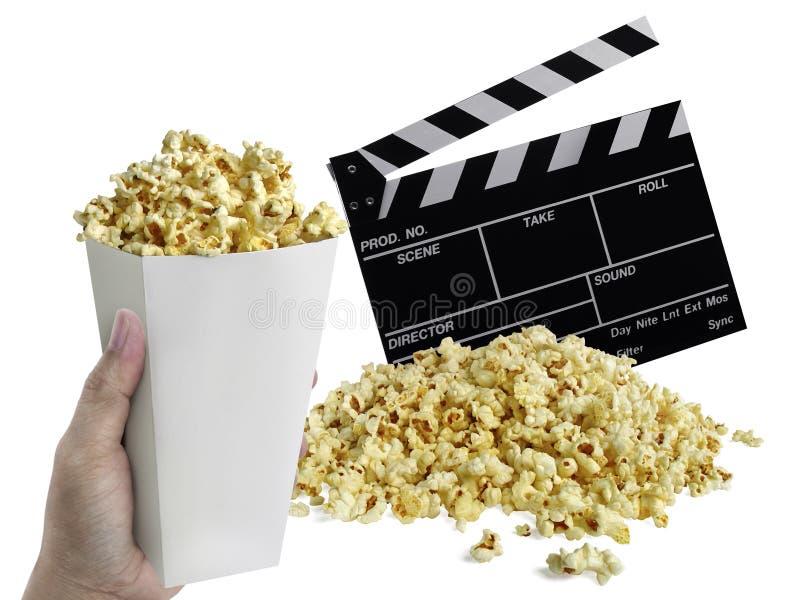 Mano con las palomitas, clapperboard de la película aisladas en blanco fotografía de archivo libre de regalías
