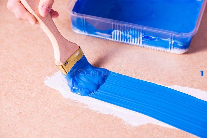 Mano con las pinturas del cepillo con la pintura azul fotografía de archivo libre de regalías