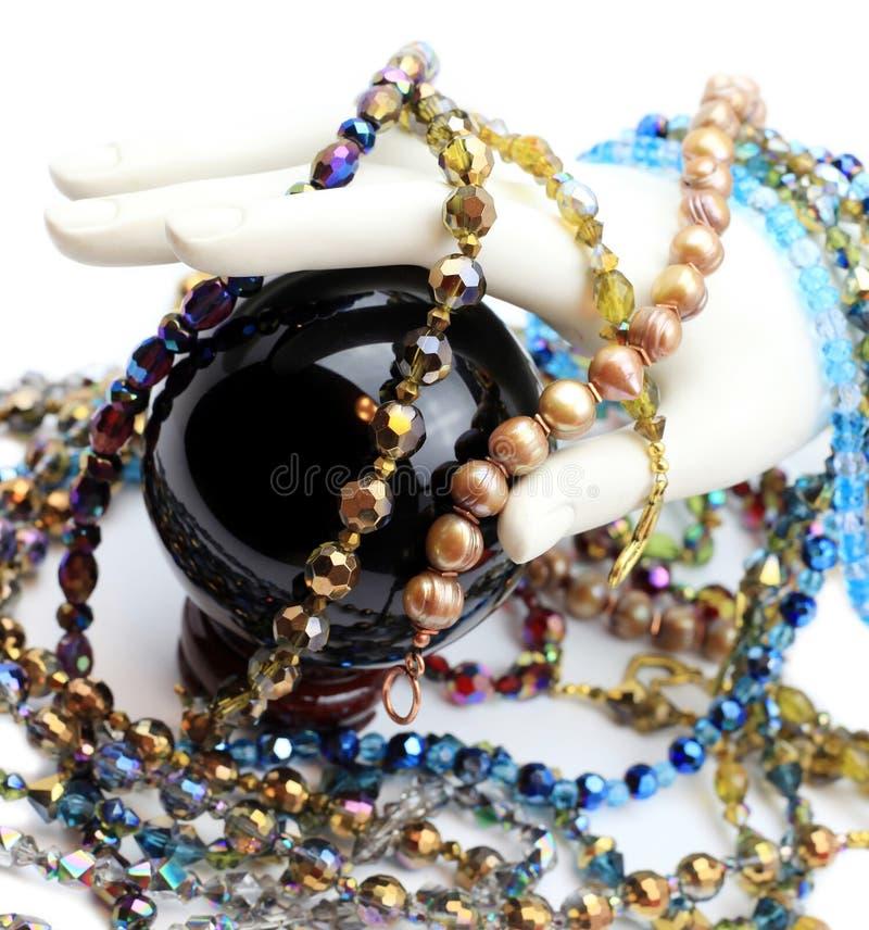 Mano con le perle, le perle e la sfera di cristallo fotografia stock