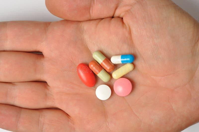 Mano con le pillole immagine stock