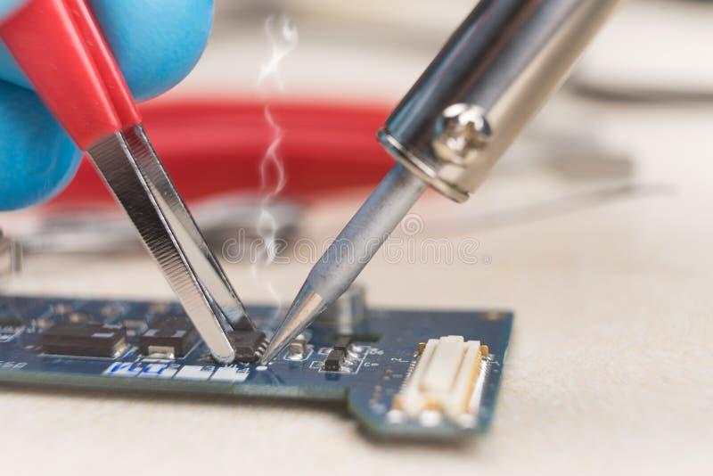 Mano con le pinzette che tengono il chip, lega per saldatura del saldatoio sul posto Riparazione del calcolatore macrofotografia  immagini stock libere da diritti