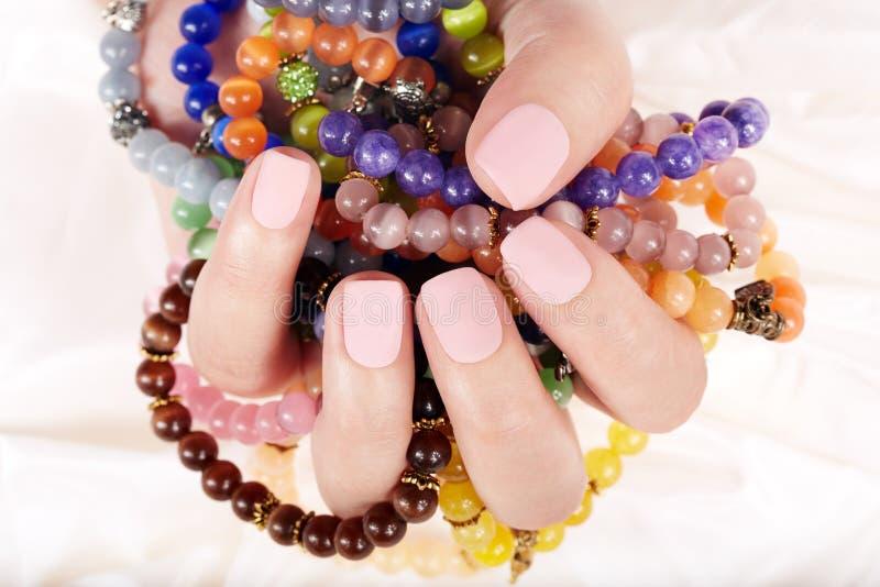 Mano con le unghie dipinte opache ed i braccialetti variopinti immagine stock