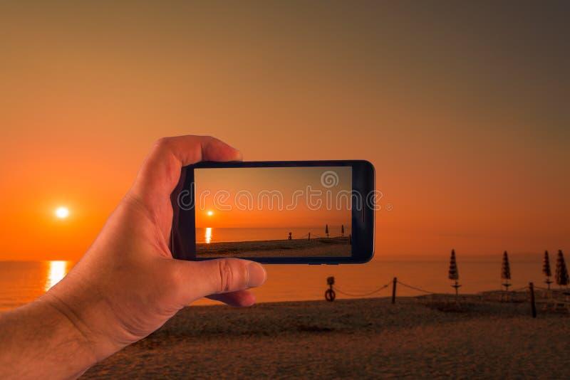 Mano con lo smartphone che prende le immagini in un giorno soleggiato fotografia stock