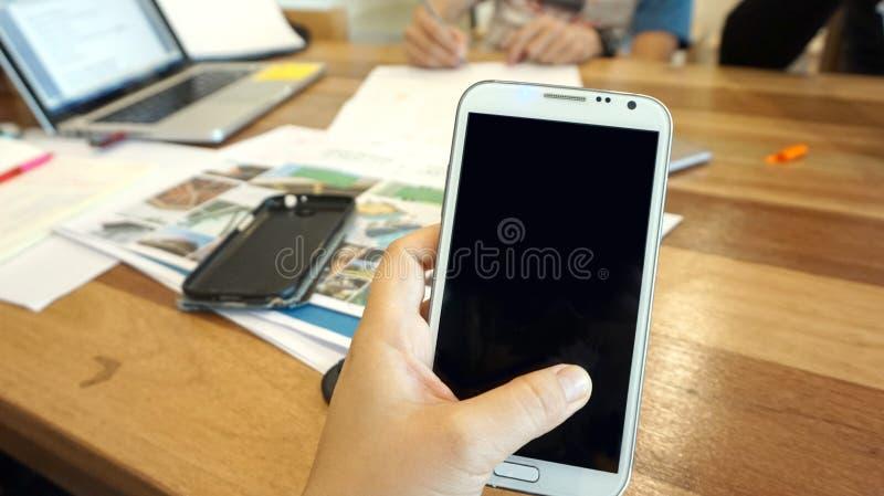 Mano con lo smartphone sulla tavola di funzionamento immagini stock libere da diritti