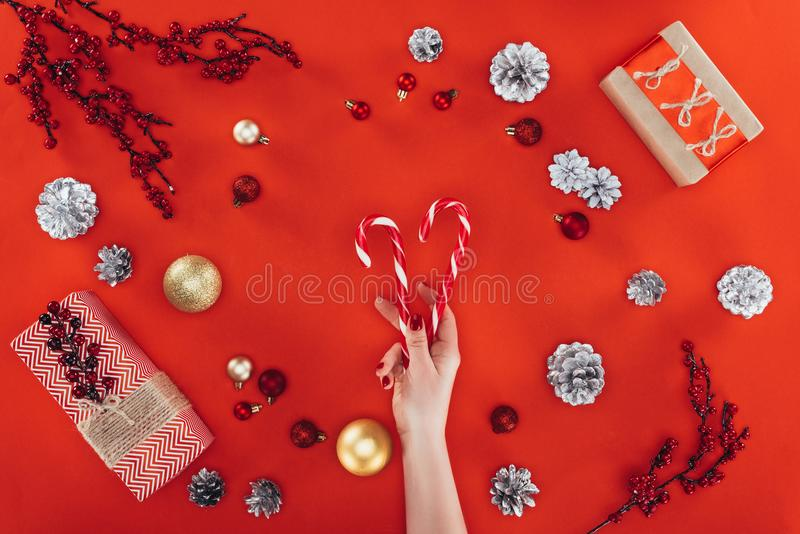 Mano con los bastones de caramelo en el christmastime foto de archivo libre de regalías