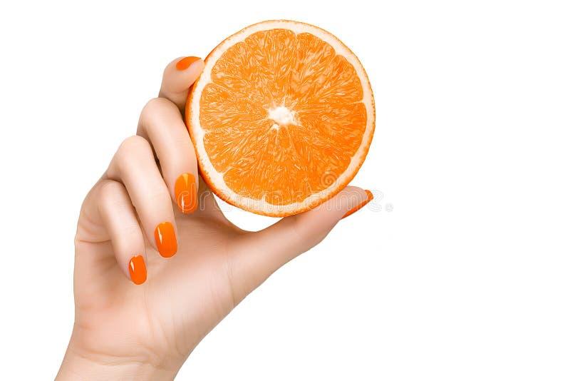 Mano con los clavos anaranjados que sostienen una fruta anaranjada fotos de archivo