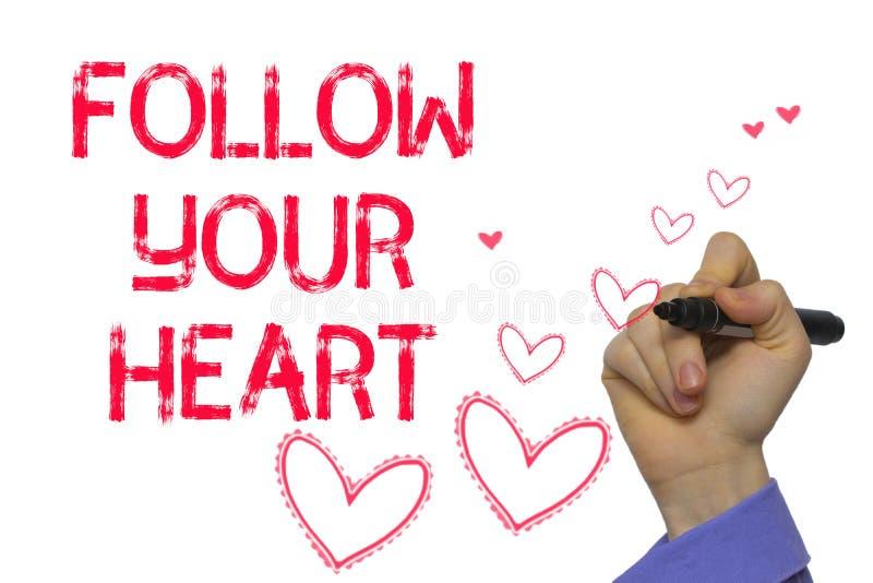 Mano con scrittura dell'indicatore: Segua il vostro cuore fotografia stock