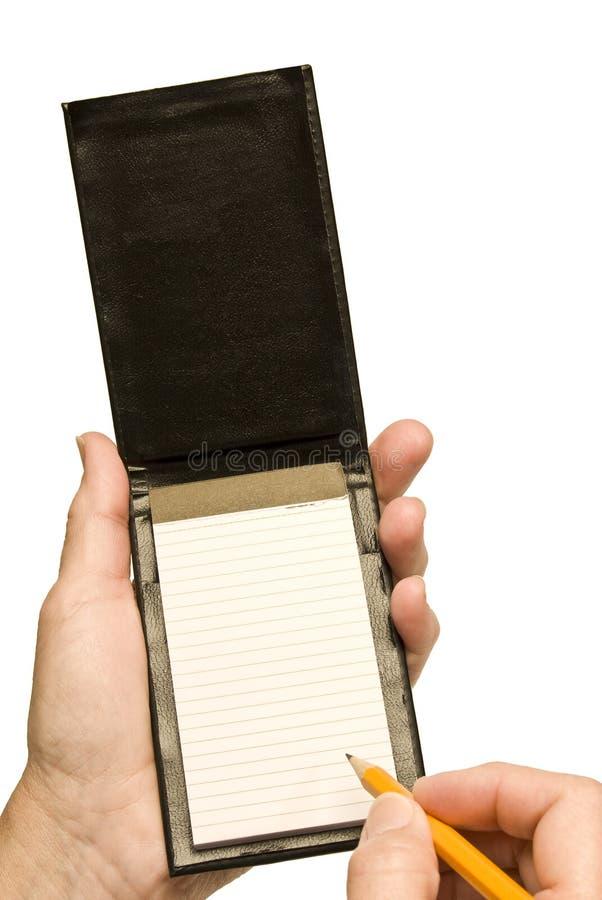 Mano con scrittura della matita in piccolo taccuino in bianco fotografia stock libera da diritti