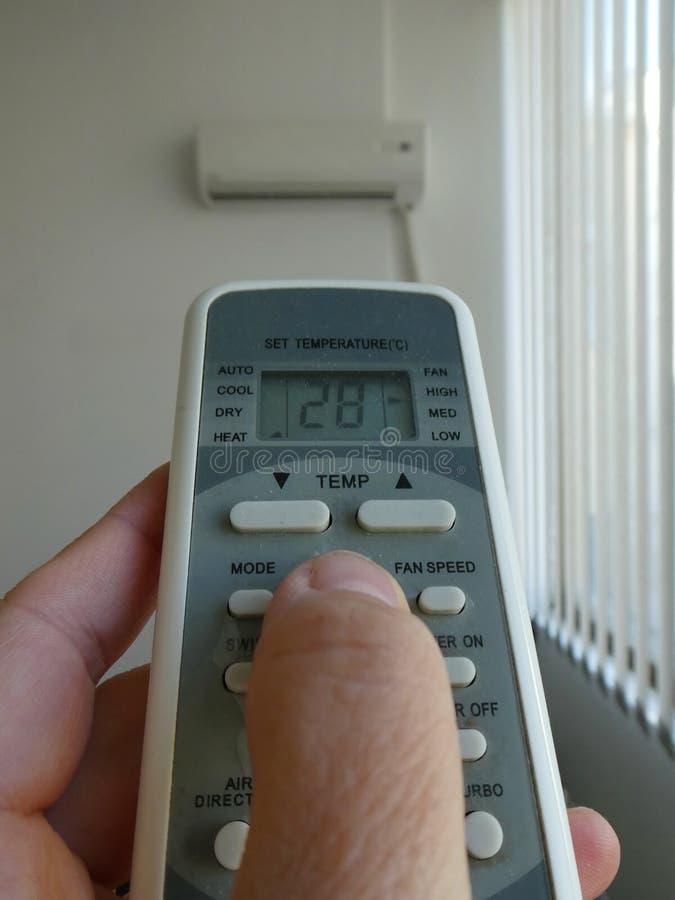 Mano con telecomando diretto sul condizionatore per riscaldare immagine stock