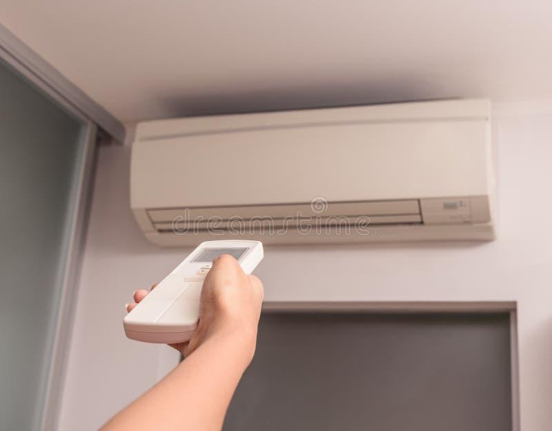 Mano con teledirigido dirigido en el acondicionador de aire fotos de archivo libres de regalías