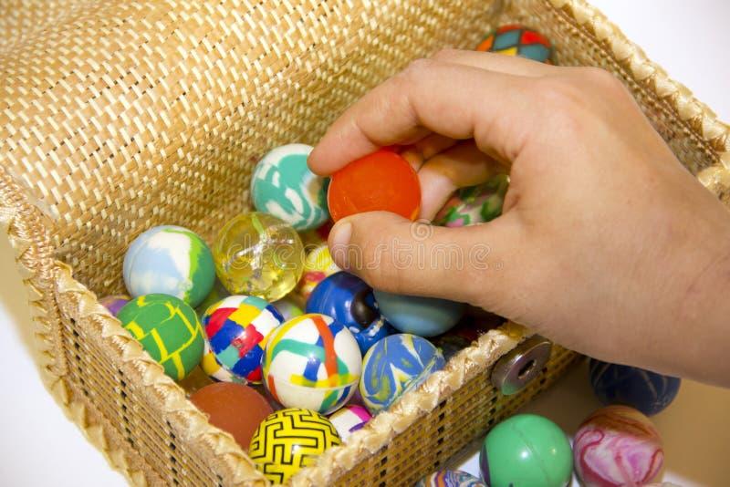 Mano con una bola y caja por completo de bolas coloridas fotografía de archivo