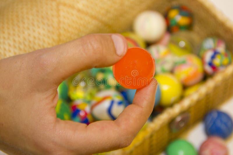 Mano con una bola y caja por completo de bolas coloridas fotos de archivo