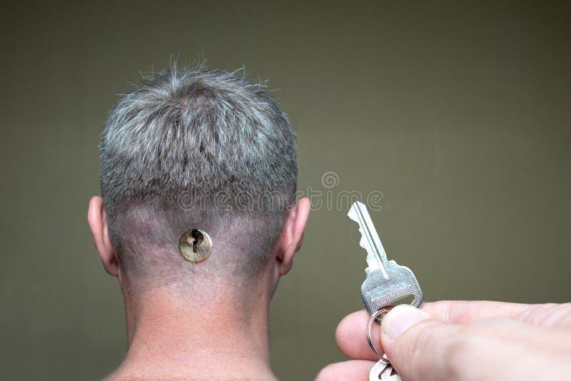 Mano con una llave cerca de una cabeza masculina con un ojo de la cerradura en la parte posterior de la cabeza imagenes de archivo