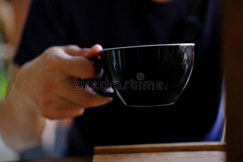 Mano con una taza de café. Bebida de menú para relajarse en mesa de madera Textura y espacio para el texto. Diseño de diseño d fotografía de archivo