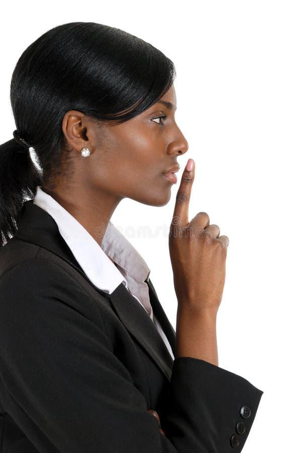 Mano confidente de la mujer de negocios en los labios para el silencio foto de archivo