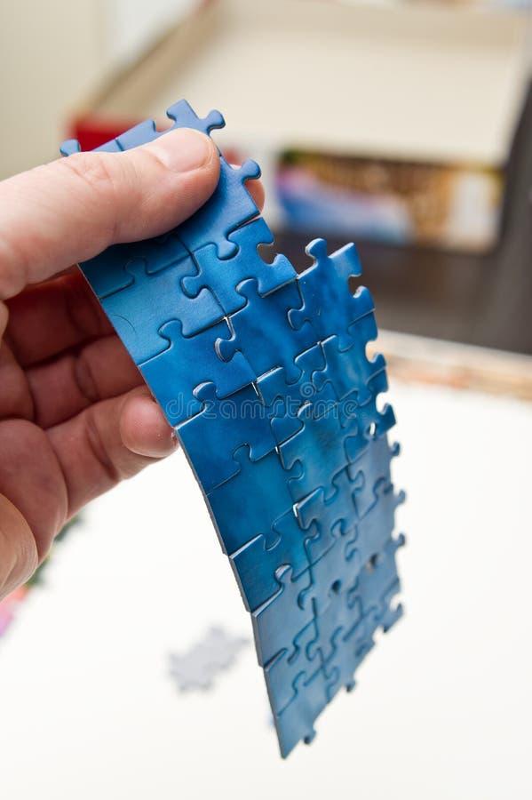 Mano contenente una striscia di pezzi di puzzle blu immagini stock libere da diritti