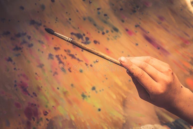 Mano creativa del pintor con la escuela de arte de la creatividad del concepto del fondo de la pintura del extracto de la brocha foto de archivo libre de regalías
