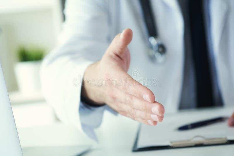 Mano d'offerta di medico maschio della medicina alla scossa in primo piano dell'ufficio Accogliendo ed accogliendo favorevolmente immagine stock