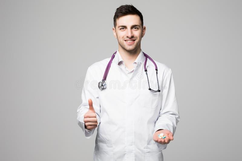 Mano d'offerta incoraggiante dell'erba medica o di medico in pieno di varie pillole che mostrano come il gesto su gray immagini stock